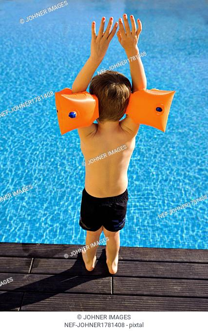 Boy wearing inflatable armbands on edge of swimming-pool