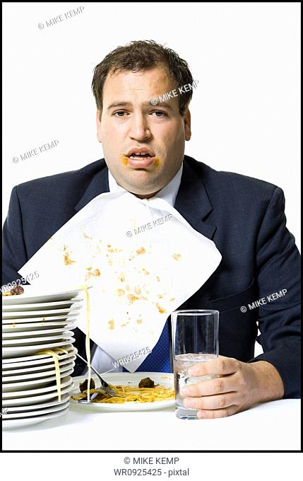 Overweight businessman gorging himself on spaghetti