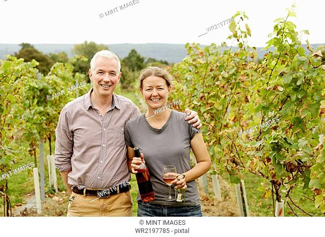 A couple, vineyard founder and her partner standing among the rows of vines
