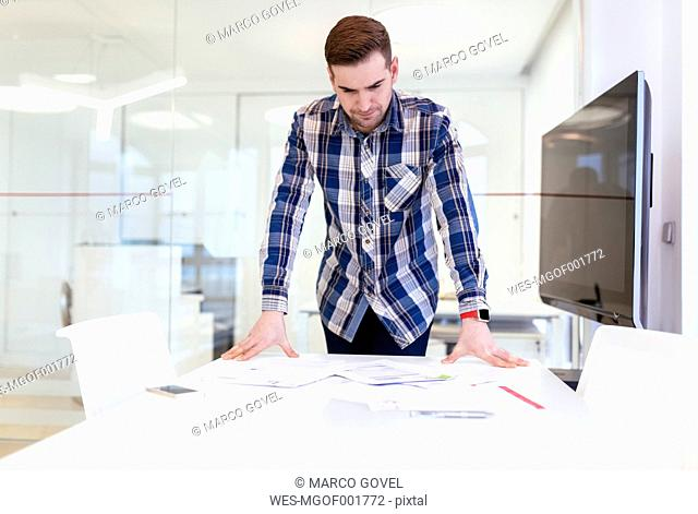 Young man at desk in office looking at documents