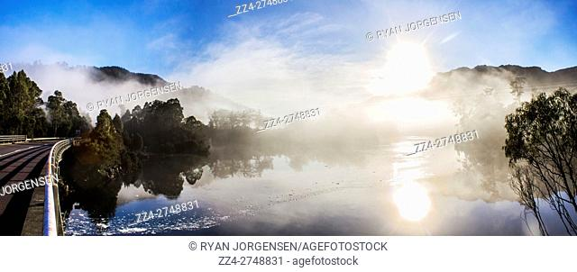 Scenic panorama landscape of early morning mist on Lake Rosebery, in Tullah Tasmania, Australia with the sun bursting above the mountain peaks and reflecting...