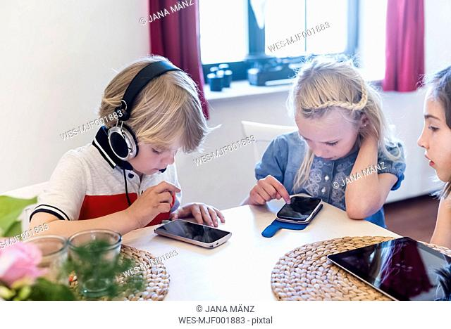 Three children with mobile devices