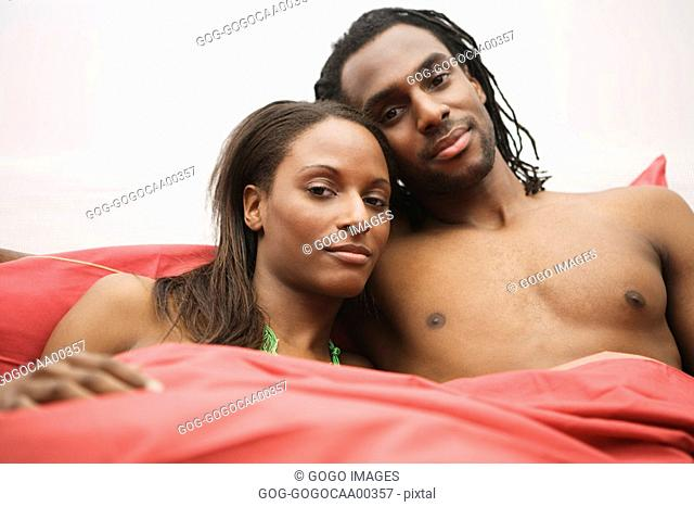 African couple sitting in bed