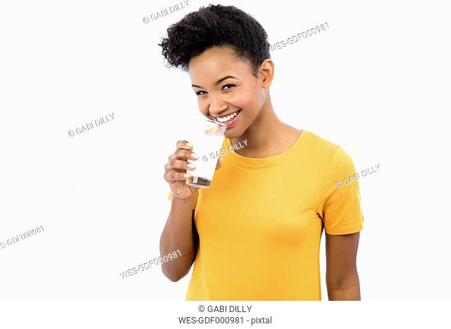 Portrait of smiling young woman drinking glass of milk in front of white background