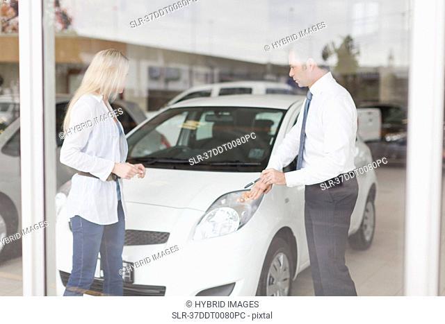 Car salesman showing car to customer