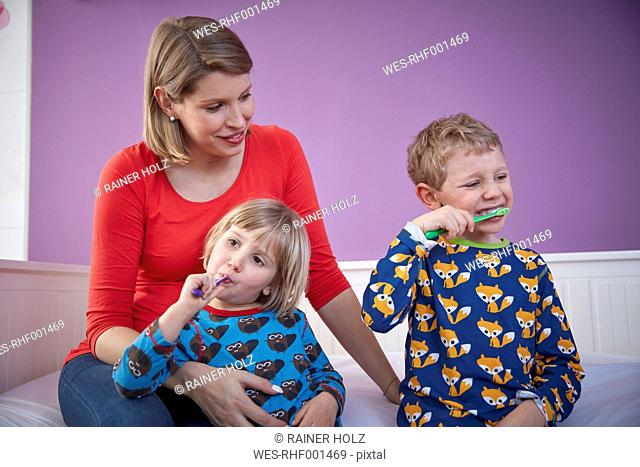 Mother with two children brushing teeth