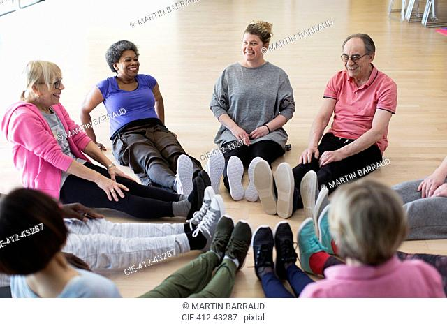 Instructor and active seniors stretching legs in circle in exercise class