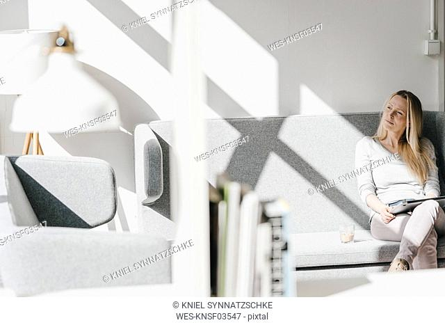 Woman sitting on couch with laptop