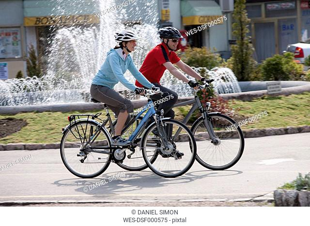 Italy, Trento, Man and woman cycling by fountain in Arco
