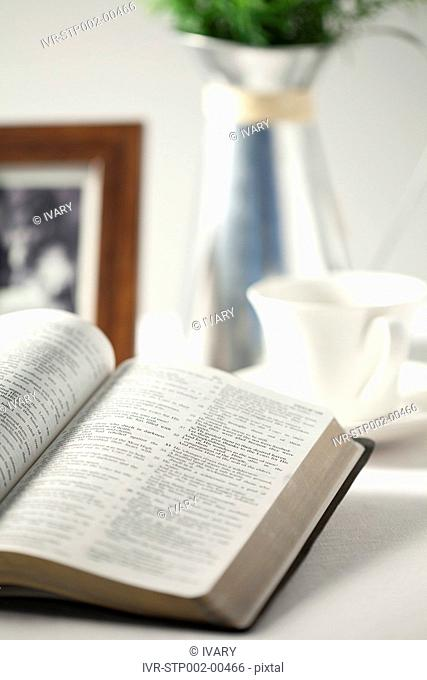 Focus on bible with vase, photo frame and cup in background