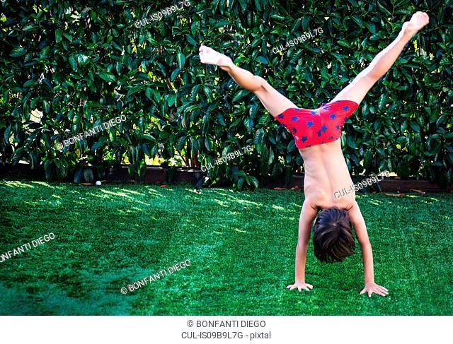 Boy doing handstand on grass