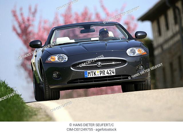 Jaguar XK 4.2LV8 Convertible, model year 2006-, anthracite, open top, driving, diagonal from the front, frontal view, country road