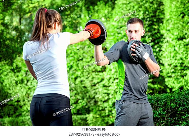 Young sports couple training to box in the park