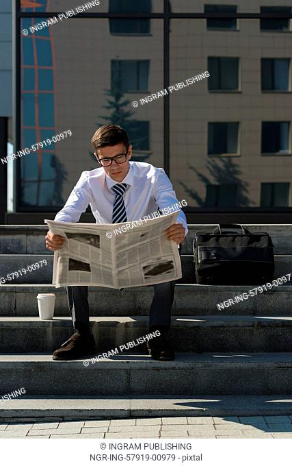Well dressed business man reading newspaper sitting on a street sidewalk