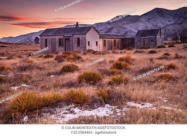 Dawn light, 1939 farm cottage (still in use as tea room for shearers), early winter snowfall on Hawkdun Range, St Bathans, Central Otago