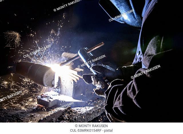 Worker welding metal in foundry
