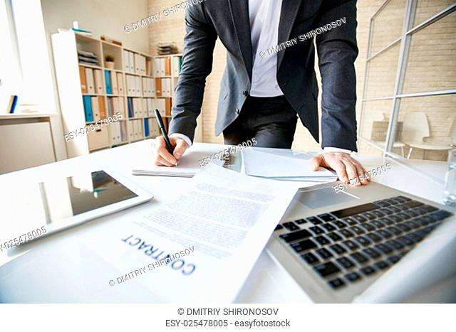 Male employee in suit making notes at workplace