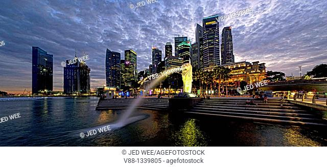 Singapore skyline and Merlion statue in evening twilight, viewed from Merlion Park, Singapore