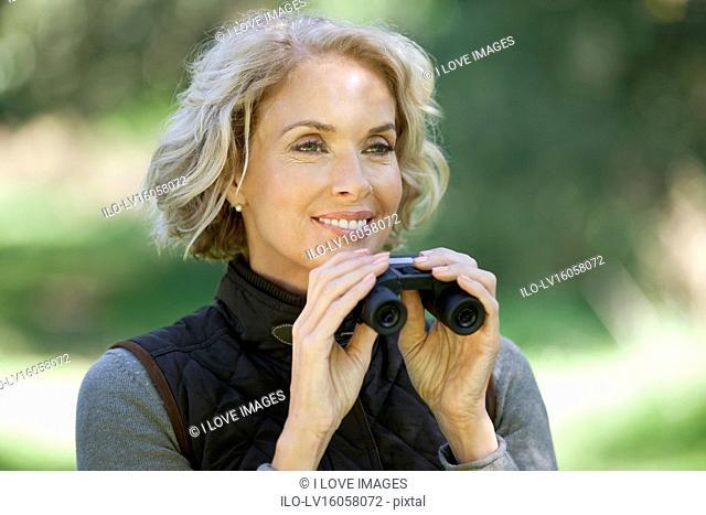 A mature woman outdoors, holding a pair of binoculars