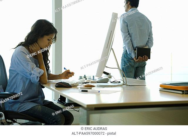 Woman working at desk at home, husband looking out window in background