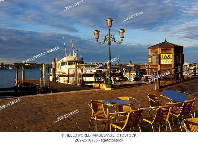 Warm dawn sunlight on the Venetian waterfront with water taxi office, alfresco tables and chairs and moored boats, Venice, Veneto, Italy, Europe