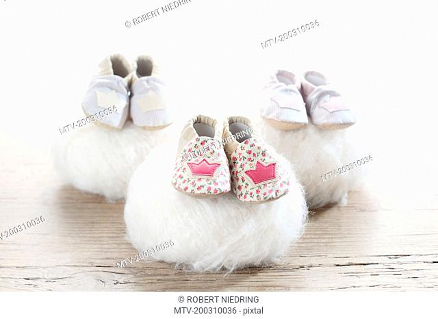 Three pairs of baby shoes on woolen soft balls, Bavaria, Germany