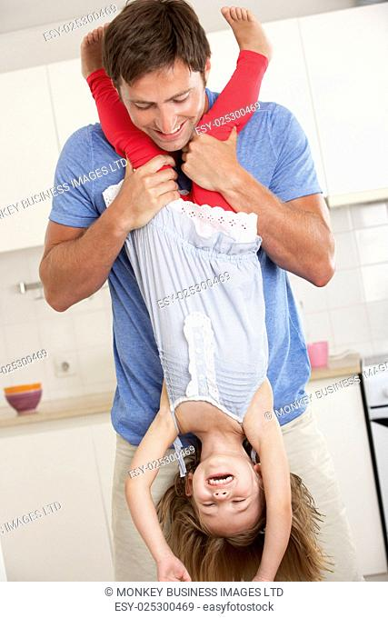 Father Holding Daughter Upside Down At Home