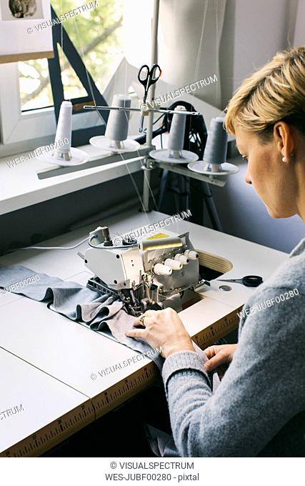 Woman using sewing machine on table in studio