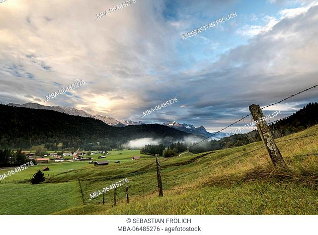 mossy pasture fence in a mountain pasture, in the background the hamlet Gerold, fog and clouds, as well as the Zugspitze massif in the morning light