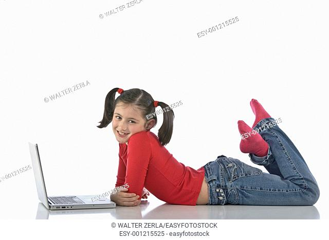 Adorable caucasian little girl lying with laptop