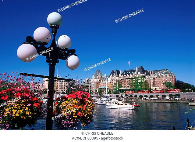 Flower baskets hanging with the Empress Hotel beyond, Victoria, Vancouver Island, British Columbia, Canada
