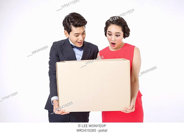 Portrait of young couple holding a delivery box and looking down with surprised faces