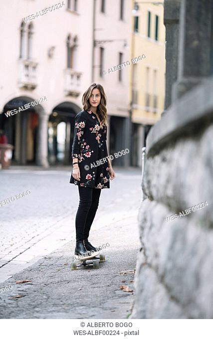Portrait of fashionable woman on skateboard
