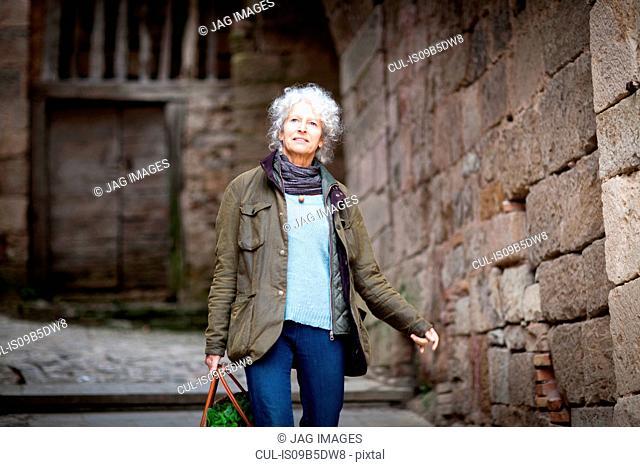 Woman walking in rural street, Bruniquel, France