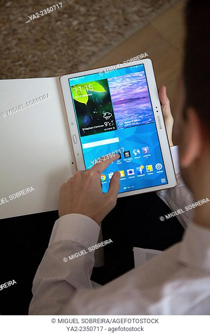 Man with Handheld Samsung 10.5 Tab S on Couch - UK