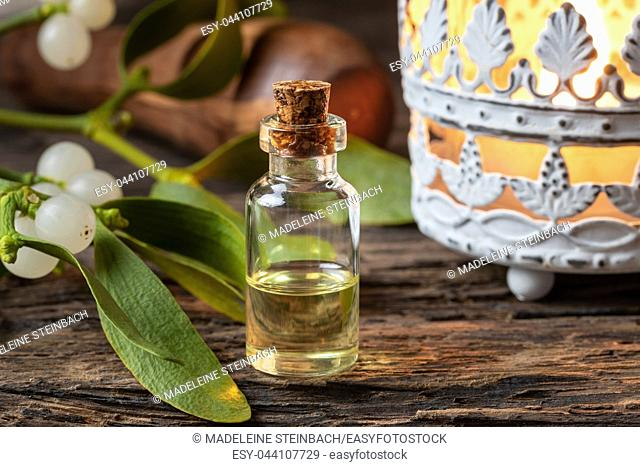 A bottle of essential oil with fresh mistletoe twigs