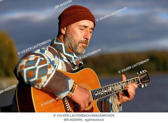 Man plays guitar on a boat landing stage at the lake, Mecklenburg Lake District, Mecklenburg-Western Pomerania, Germany