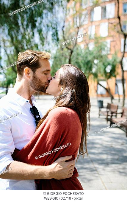 Happy couple kissing and hugging in the street