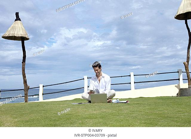 A man sitting cross-legged on the grass and working on a laptop