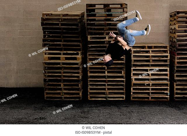 Young male street dancer somersaulting in front of stacked pallets