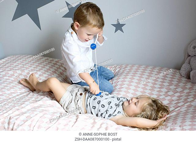 Children playing doctor with toy stethoscope