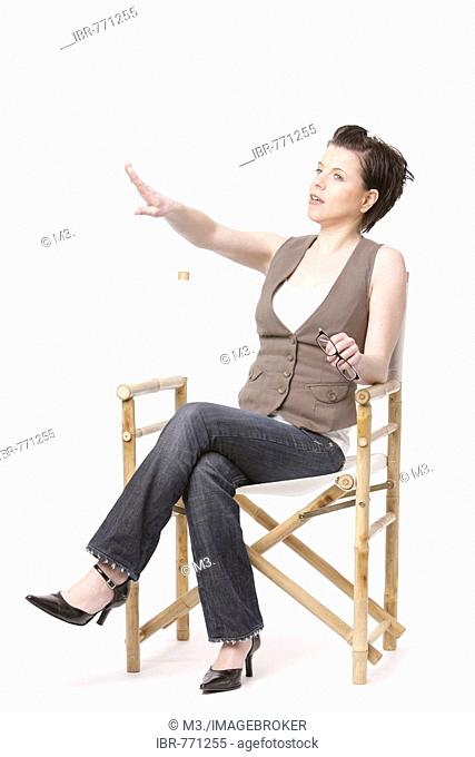 A woman sitting in a director's chair and giving orders
