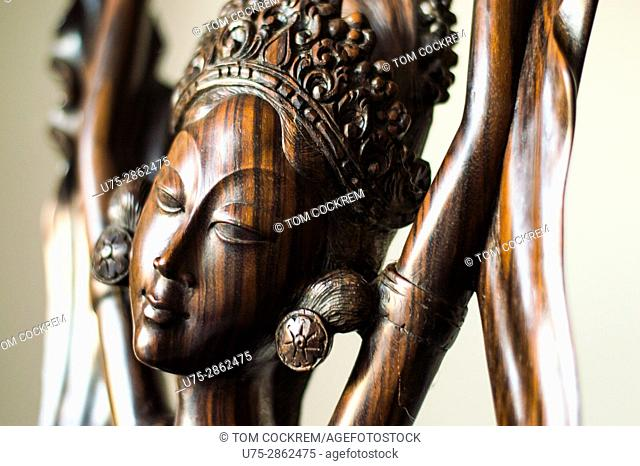 Carved wooden statue of Indionesian goddess, in studio setting