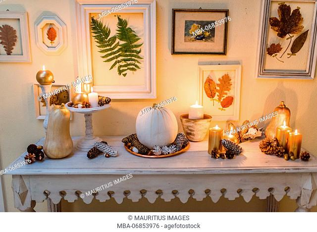 Console table, autumnal decoration, candles, picture frames, leaves