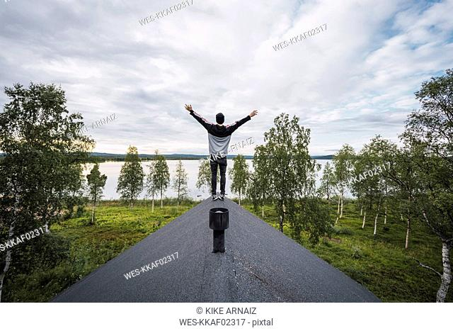 Finland, Lapland, man standing on roof of a house at a lake with raised arms