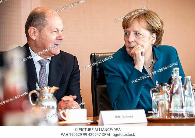 29 May 2019, Berlin: Chancellor Angela Merkel (CDU) talks to Olaf Scholz (SPD), Federal Minister of Finance, before the start of the Federal Cabinet meeting at...