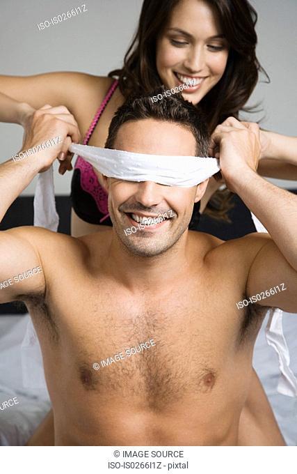 A woman blindfolding a man