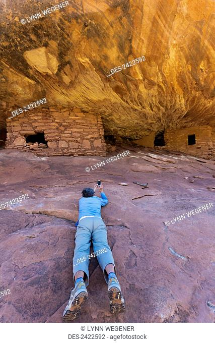 A female tourist takes photos with a smart phone of the House on Fire Anasazi ruin in Mule Canyon; Utah, United States of America