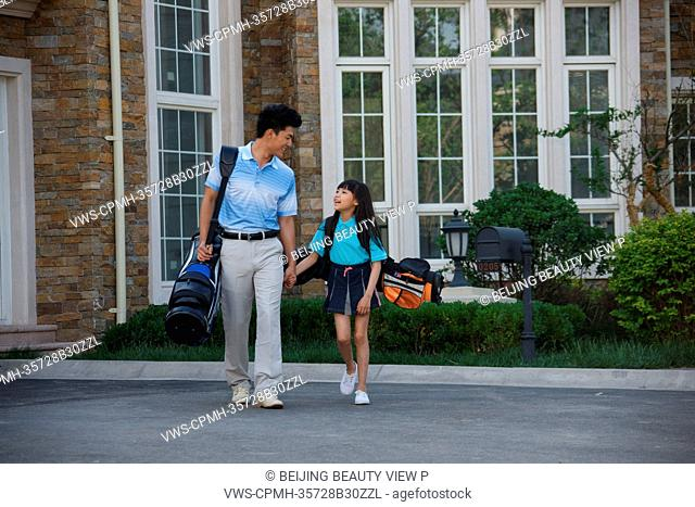 Oriental father and daughter with golf bag in front of villa