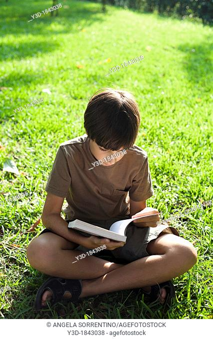 Young boy reads book in outdoor park